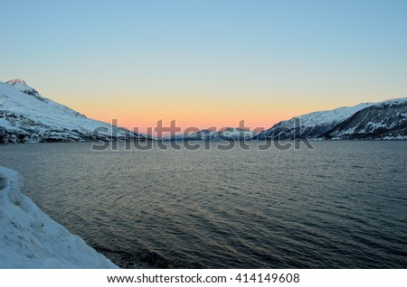 Vibrant colours on dawn sky over cold arctic fjord water and majestic snowy mountain range in winter
