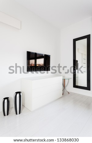 Vibrant cottage - white commode and black tv - stock photo