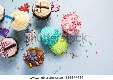 Vibrant cupcakes on blue background, party food concept, overhead - stock photo