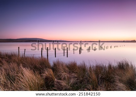Vibrant dusk over Dozmary Pool a small natural lake on Bodmin Moor in Cornwall - stock photo