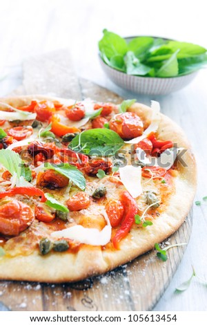 Vibrant handmade oven baked pizza with roasted tomatoes, peppers, capers, basil and shaved cheese - stock photo