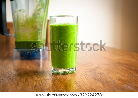 Vibrant healthy green smoothie with a blender in the background on a wooden table - stock photo
