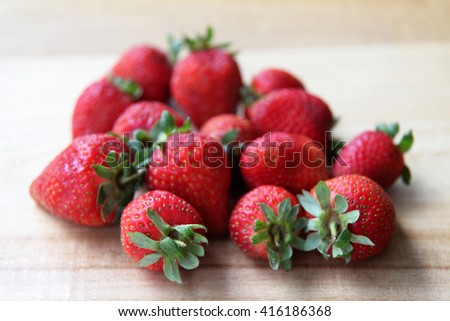 Vibrant, juicy red strawberries with green leaves on a wooden surface - stock photo