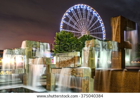 Vibrant Lights Illuminate Modern Fountain Sculpture in Night Scene with Seattle Great Wheel in Seattle, Washington - stock photo