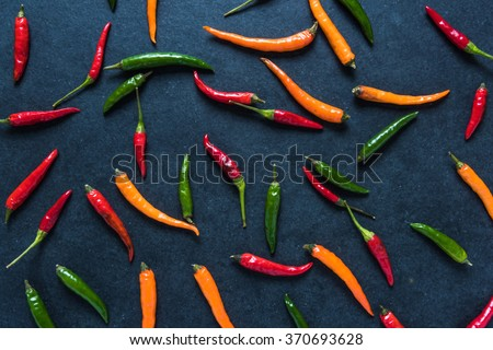 Vibrant peppers on dark slate, lay flat from above - stock photo