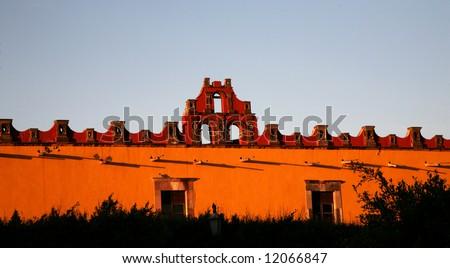 Vibrant Red and Yellow Colored Building College, Civic Civica Plaza, San Miguel de Allende, Mexico - stock photo