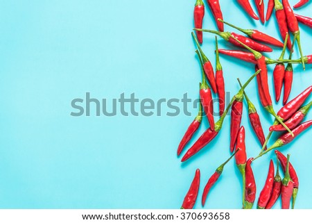 Vibrant red chili on blue background, lay flat from above - stock photo