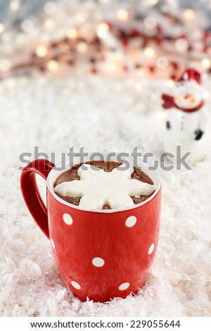 Vibrant red cup of hot chocolate with snow flake shape of whipped cream. Snowman and Christmas lights in the background. Extreme shallow depth of field. - stock photo