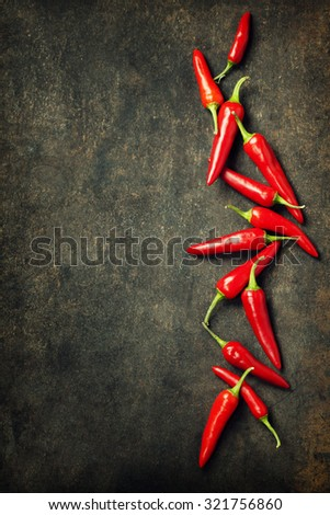 Vibrant red mexican hot chilli pepper on old background - stock photo