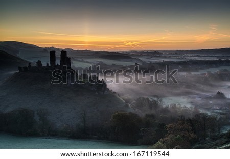 Vibrant sunrise over medieval castle ruins with fog in rural landscape - stock photo
