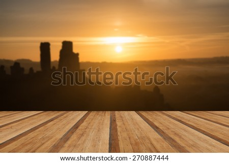Vibrant sunrise over medieval castle ruins with fog in rural landscape with wooden planks floor