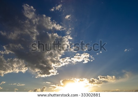 Vibrant sunset with sunbeams across blue sky with scattered white clouds