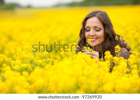 Vibrant yellow canola field and cheerful girl, spring feeling from Latvia, Baltic states - stock photo