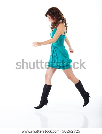 Vibrant young adult caucasian woman in a short turquoise dress with black boots and a brunette wig, shot on a white background. Not isolated.