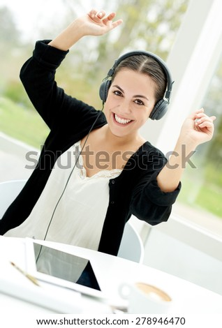 Vibrant young woman enjoying her music downloaded on her tablet-pc lifting her arms as she sways to the beat over her stereo headphones - stock photo