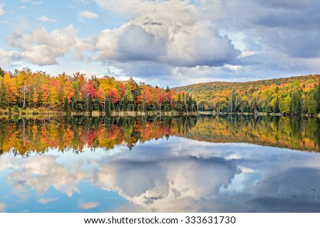 Vibrantly colorful fall foliage and white clouds in a blue sky are reflected on Lake Plumbago at Alberta in Upper Peninsula Michigan. - stock photo
