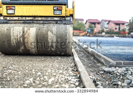 vibration roller compactor at road construction and repiaring asphalt pavement. compactor working on site - stock photo