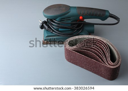 Vibratory sander with sandpaper on grey wooden table - stock photo
