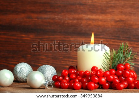 viburnum and lit the candle with a sprig of fir with Christmas balls on wooden table - stock photo