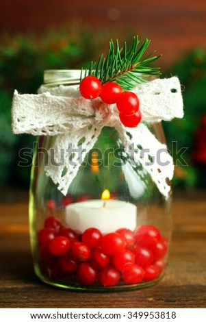 viburnum in a jar with a candle and a sprig of spruce on a wooden table - stock photo