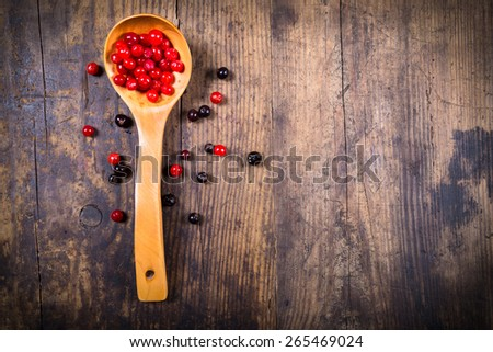 viburnum in spoon and black currant on wooden background with empty copy space - stock photo