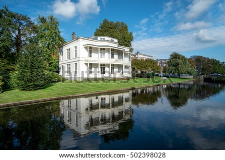 Vicorian white house reflection on a calm canal water under a very sunny and blue sky day at The Hague, Netherlands