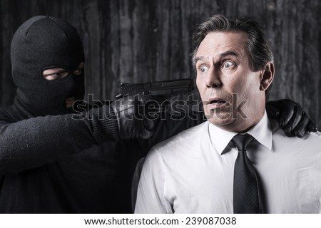Victim of violence. Shocked businessman caught by a criminal aiming his head with gun  - stock photo