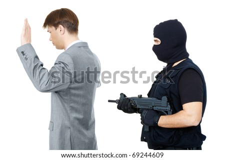 Victim standing with hands raised while mafia representative pointing gun at them behind - stock photo