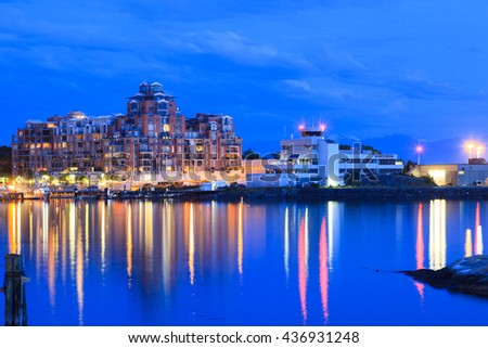 VICTORIA, BC, CANADA - MAY 17 2016: Night view of the Inner Harbor Downtown. Tourists strolling the causeway. This waterfront is the location of many tourist attractions and recreational activities.