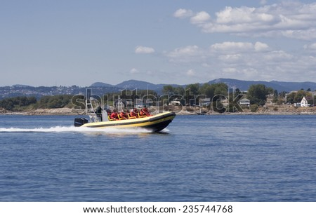 VICTORIA, CANADA - AUGUST 2, 2005: People enjoying Ride with Inflatable Boat after Whale Watching in the Pacific Ocean. - stock photo