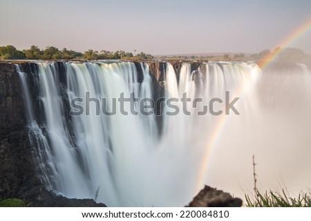 Victoria Falls, rainbow and silk water, long exposure photo, Zimbabwe side - stock photo