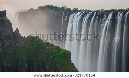 Victoria Falls sunset, long exposure view from Zambia with rocks - stock photo