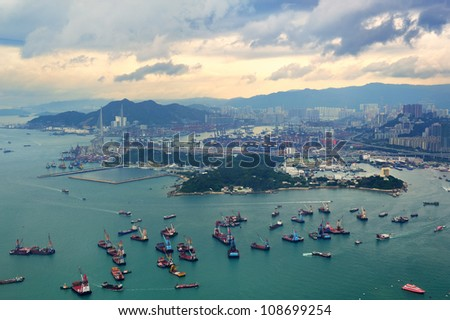 Victoria Harbor aerial view and skyline in Hong Kong with urban skyscrapers and boats. - stock photo