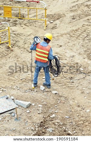 VICTORIA, HONG KONG - JAN 8: worker with electric cable and helmet on Jan 8, 2010 in Victoria, Hong Kong. Helmet and safety west is a must in Hong Kong for workers  and checked by police.