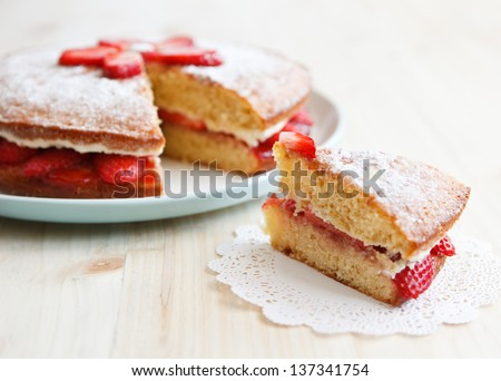 Victoria sponge cake with strawberries, jam and whipped cream with a cut out piece on a wooden table - stock photo