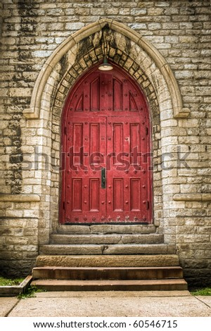 Victorian architectural detailed doorway with a red door and steps surrounded by ornate stonework. Outdoor church exterior.