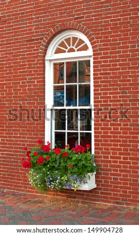 Victorian brown brick house window and flowers - stock photo