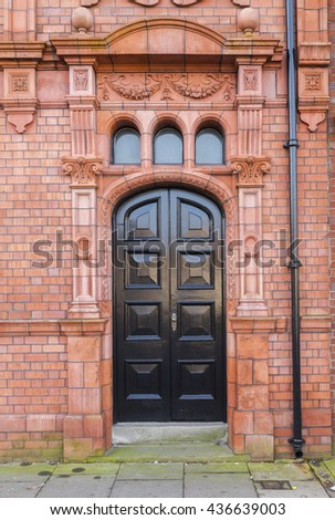 Victorian door surrounded by ornate red brick with decorative terracotta tiles.
