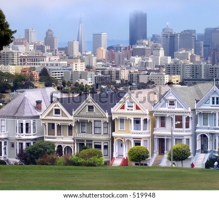 Victorian houses in San Francisco with downtown in the background - stock photo
