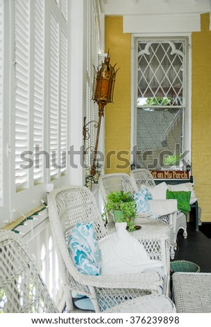 Victorian Style Porch With Wicker and Shutters