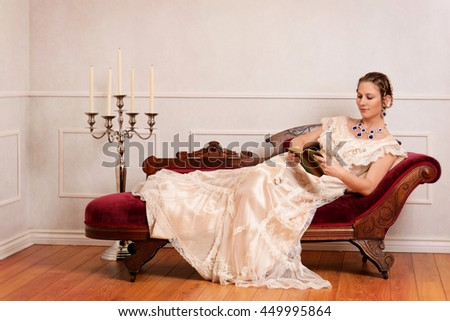 Victorian woman reading book on fainting couch - stock photo