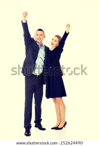 Victorious business couple with hands up. - stock photo