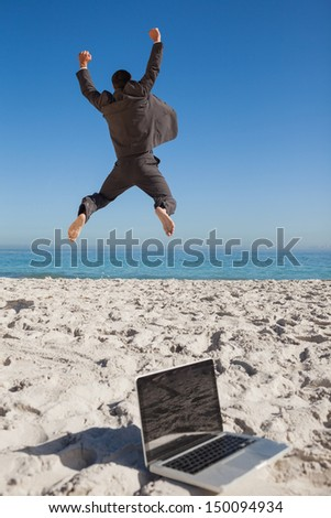 Victorious businessman in suit jumping leaving his laptop on the beach - stock photo