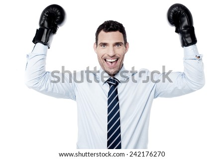 Victorious businessman raising hands with boxing gloves - stock photo