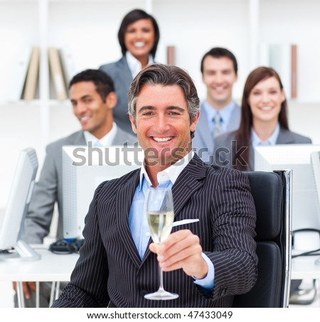 Victorious manager and his team drinking champagne in the office