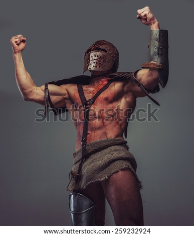 Victorious muscular gladiator with blood on his body