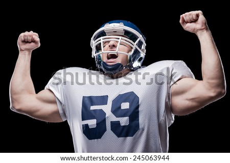 Victory!  American football player screaming and keeping arms raised while standing against black background  - stock photo