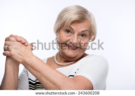 Victory is my second name. Closeup portrait of happy elderly woman with her hands clasped smiling to the camera while standing against white background - stock photo