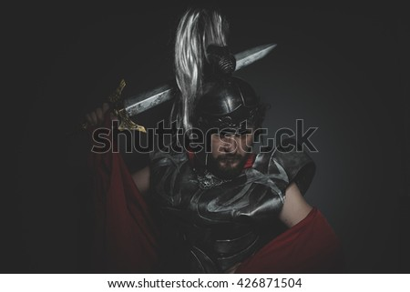 Victory, Praetorian Roman legionary and red cloak, armor and sword in war attitude - stock photo