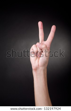 Victory sign on neutral background. Number two